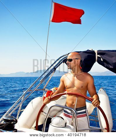 Photo of handsome muscular man at the helm of ship, sailing at Mediterranean sea, traveling the world by sailboat, male model on luxury yacht, water sport vacation, summer outdoors