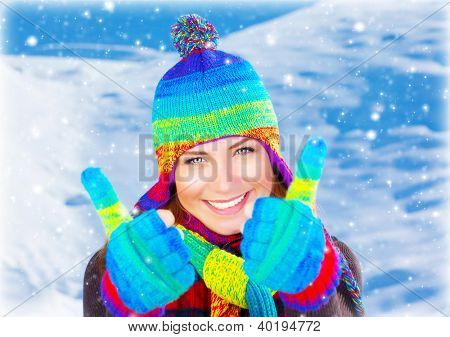 Colorful thumbs up of a happy smiling girl wearing winter clothes, beautiful female face portrait, young pretty woman with natural snow background, winter fun outdoor, happy people concept