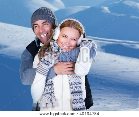 Happy couple hugs, holding hands, close up portrait, outdoor at winter snowy mountains, people over natural blue wintertime landscape background, Christmas vacation holidays, love concept