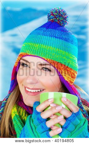 Image of beautiful girl drinking hot chocolate outdoor in winter park, pretty person having coffee, happy female teen wearing colorful hat, young pretty woman face, holding cup in hands
