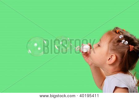 Pretty Little Girl Blowing Soap Bubbles