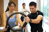 picture of vibration plate  - Instructor in a gym explains a vibration plate to a woman