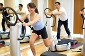 stock photo of vibration plate  - Group of two men and one woman on a vibration massage plate in a gym - JPG