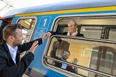 stock photo of say goodbye  - Man saying goodbye to woman on train smiling window commuter - JPG