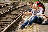 Couple resting looking at map railroad backpack travel vacation happy