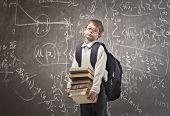 stock photo of boredom  - Child with backpack holding some school books with a blackboard in the background - JPG