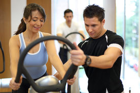 picture of vibration plate  - Instructor in a gym explains a vibration plate to a woman  - JPG