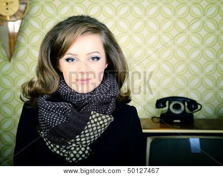 art portrait of young woman standing in room with vintage wallpaper and interior, retro stylization 60-70s
