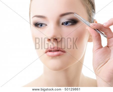 Beautiful girl plucking eyebrows with tweezers over white
