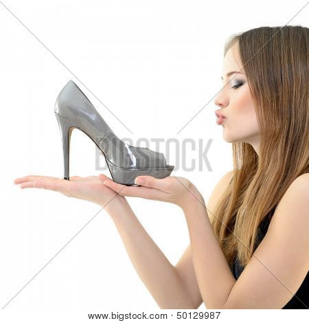 girl holding shoe in hand an looking with love on it, over white