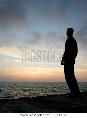 Silhouetted Young Man Watches Sunrise From A Pier.