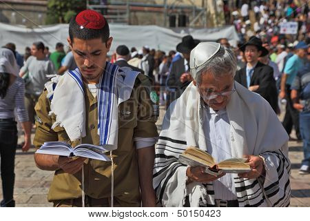 Jerusalem - October 16:  Jewish family - the father  and his son, a soldier in uniform, praying in the square near the Wailing Wall in Sukkot, October 16, 2011 in Jerusalem, Israel