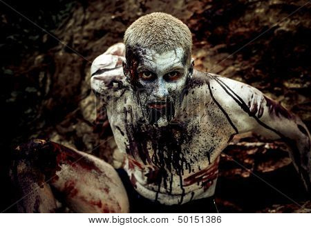 young man with a zombie body painting, covered with blood on the beach against a cliff
