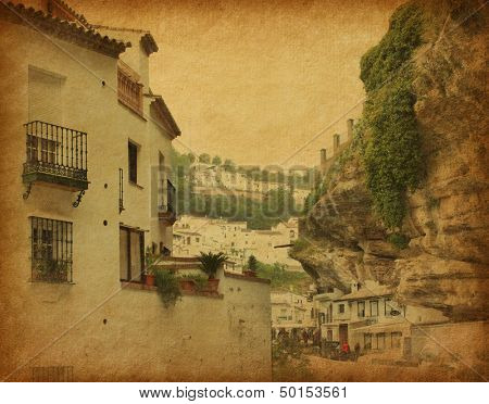Grunge image of Street in Setenil. Setenil de las Bodegas is a town  in the province of Cadiz, Spain, famous for its dwellings built into rock overhangs above the Rio Trejo. paper texture