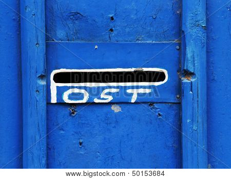 Old letterbox in blue door