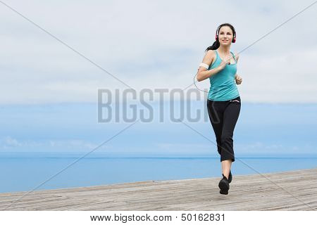Beautiful young woman jogging on a boardwalk and listen music