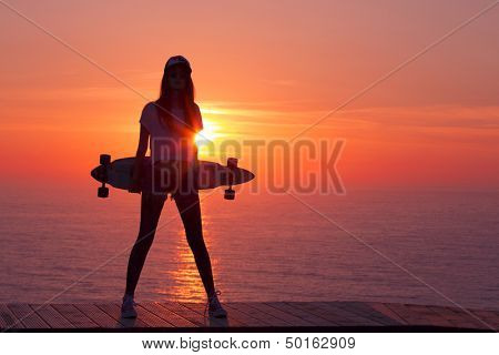 Beautiful and fashion young woman posing at teh sunset with a skateboard