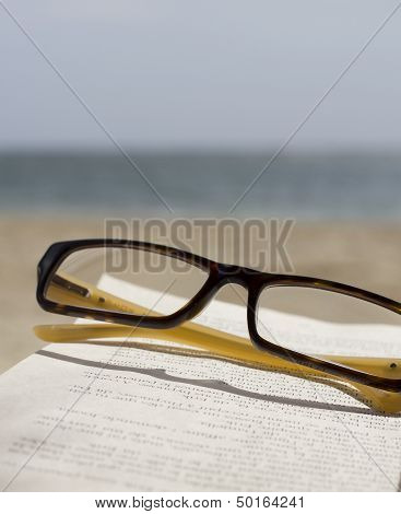 glasses book and ocean