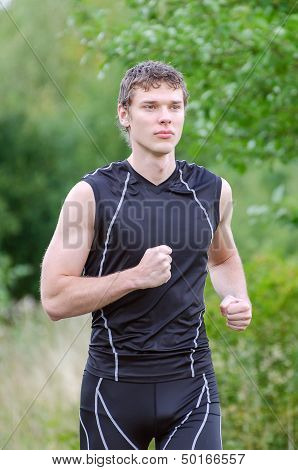 Handsome young male sportsman running in park
