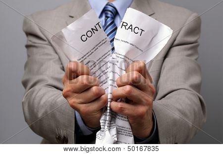 Angry businessman tearing up a document, contract or agreement