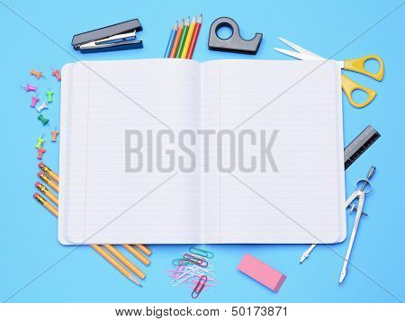 An open notebook surrounded by school supplies. Back to School concept with compass, eraser, stapler, tape dispenser, push pin, pencils, paper clips, scissors and a ruler on a blue background.