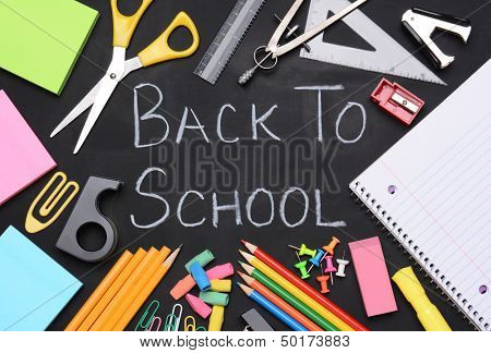 The words Back to School written on a chalkboard surrounded by school supplies including, paper, scissors, pencils, erasers, paper clips, compass, ruler, push pins and more.