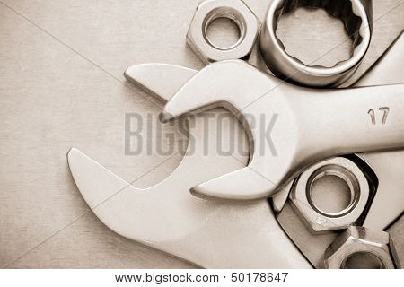 wrench tool and nut at metal  background