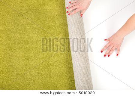 Female Hands Unrolling A Carpet