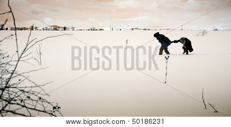 colored image of struggling couple walking field in winter time
