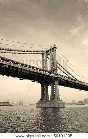 Manhattan Bridge black and white over East River viewed from New York City Lower Manhattan waterfront at sunset.