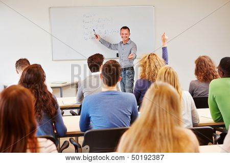 Student raising hand in school class and getting called by teacher