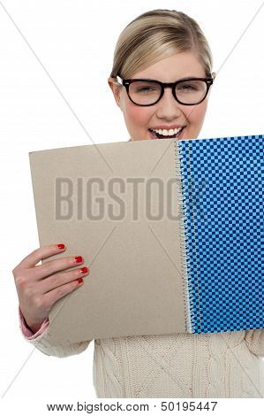 Excited Teen Girl Holding Note Book Close To Her