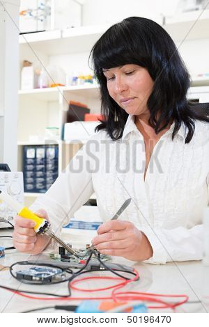woman  measures the current using a tester
