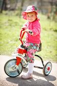 stock photo of tricycle  - little girl standing on road with her tricycle - JPG