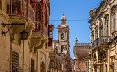 stock photo of carmelite  - Street in Mdina full of balconies and the Carmelite convent in the end of the street - JPG
