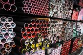 stock photo of ferrous metal  - Stack of iron pipes in an iron shop - JPG