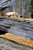 pic of log fence  - Wooden Log Fence Surrounding a Cabin in the Woods - JPG