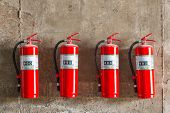 stock photo of safeguard  - Old fire extinguishers attached on the grunge concrete wall - JPG