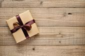 pic of gift wrapped  - Vintage gift box with bow on wooden background - JPG
