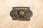 picture of pyrite  - Marcasite brooch with central gemstone set with small faceted pyrites or marcasites which have a shiny metallic lustre - JPG