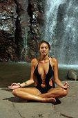 stock photo of one piece swimsuit  - Beautiful girl wearing black one piece swimsuit meditating in lotus yoga pose in front of waterfall - JPG