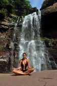 pic of one piece swimsuit  - Beautiful girl wearing black one piece swimsuit meditating in lotus yoga pose in front of waterfall - JPG