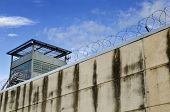 stock photo of freedom tower  - The prison wall and barbed wire in cloudy day - JPG