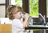 stock photo of drinking water  - Portrait of little girl having drink in domestic environment - JPG