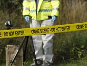pic of safety barrier  - Detective checking for evidence behind a crime scene barrier - JPG