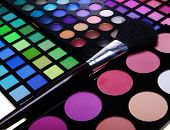 image of cosmetology  - multicolored eye shadows with cosmetics brush - JPG