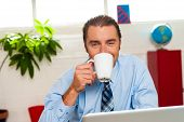 Smiling Male Manager Enjoying Hot Coffee