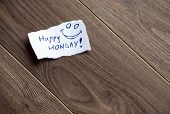 stock photo of wood pieces  - Happy Monday written on piece of paper on a wood background - JPG