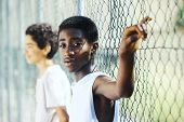 image of chain link fence  - Young African boys leaning up against a chain link fence - JPG