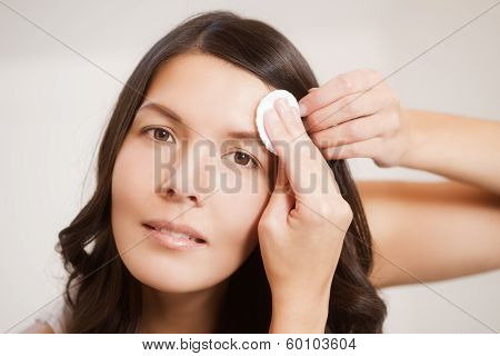 Woman Cleaning Her Skin With A Cotton Pad